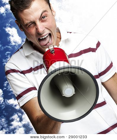 portrait of young man shouting with megaphone against cloudy sky background