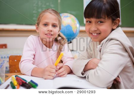 Schoolgirls drawing while looking at the camera in a classroom