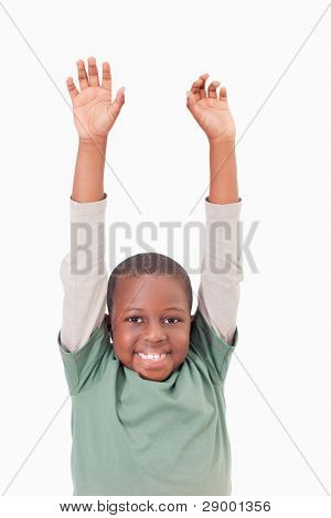 Portrait of a boy raising his arms against a white background