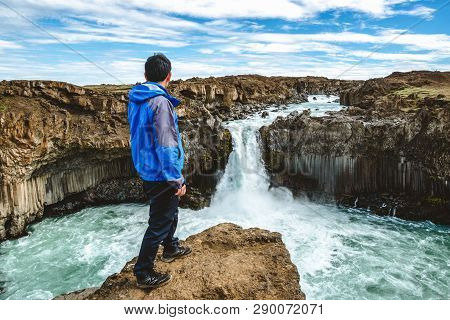 poster of Traveler Hiking In Icelandic Summer Landscape At The Aldeyjarfoss Waterfall In North Iceland. The Wa