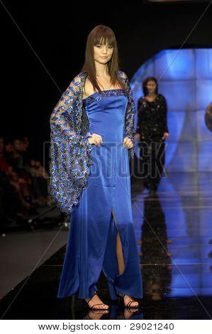 Fashion model posing in fancy silk dress on runway