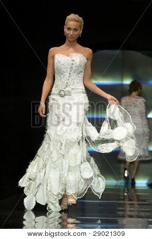 Fashion model in wedding dress walking down the runway