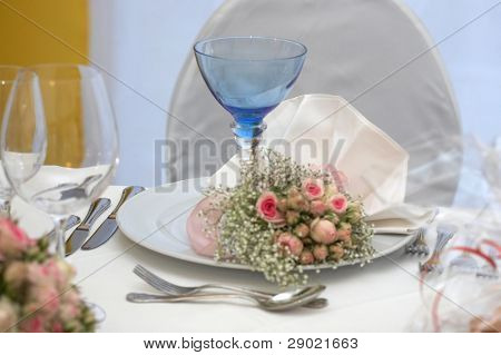 Table set for a wedding dinner. Shallow depth of field, focus on glass.