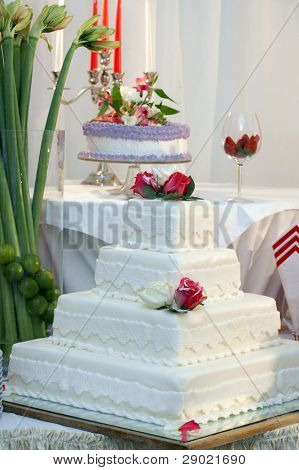 A four tiered wedding cake with white icing and roses