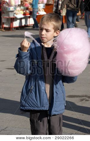 Boy eating cotton candy in the street