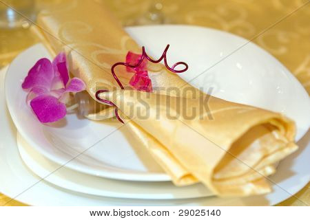 Napkin and orchid flower in the plate