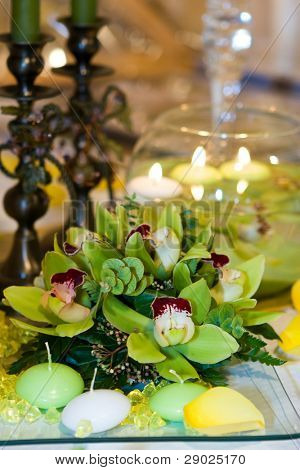 Green orchid arrangement and candles in the water