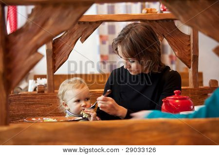 Young Mother Feeds Her Daughter