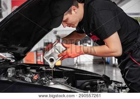 poster of Mechanic Is Pouring Oil Into Engine. Car Hood Is Open. Change The Oil.