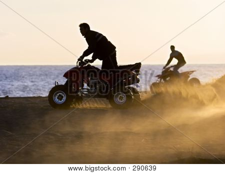 Young Men On Quad Bikes On Sandy Beach During Sunset