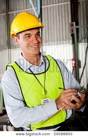 male caucasian technician taking machine gauge reading