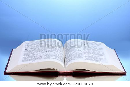 Open book on reflective surface of table on blue background