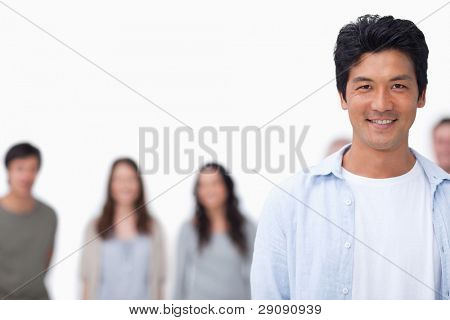 Smiling young man with friends standing behind him against a white background