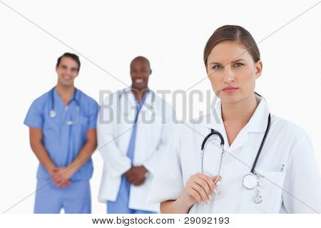 Serious looking female doctor with male colleagues behind her against a white background