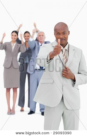 Tradesman with team behind him giving thumb up against a white background