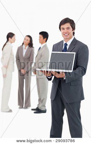 Smiling salesman showing laptop screen with team behind him against a white background