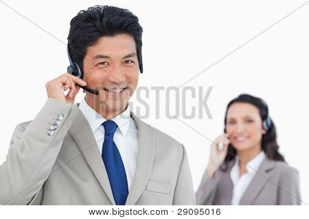 Smiling call center agent with colleague behind him against a white background