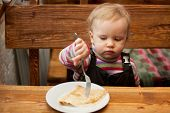 stock photo of ruddy-faced  - Blond little girl eats pancakes at a wooden table - JPG