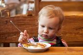 image of ruddy-faced  - Blond babe eats pancakes at a wooden table in a cafe - JPG