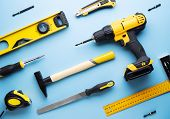 Creative Provocation: A Flat Layout Of Yellow Hand Tools On A Blue Background. poster