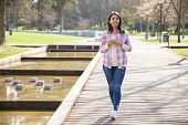 Positive Beautiful Girl Walking Towards Boyfriend. Young Woman In Checked Shirt And Jeans Holding Ce poster