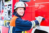 Man of the fire department getting on fire engine and smiling poster