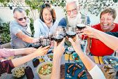 Happy Senior Friends Toasting With Red Wine Glasses At Dinner Time Outdoor - Mature People Having Fu poster