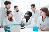 Focused and serious female and male chemists in lab coats and safety goggles making experiments poster