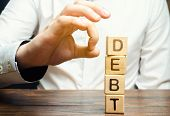 Businessman Removes Wooden Blocks With The Word Debt. Reduction Or Restructuring Of Debt. Bankruptcy poster