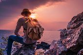 A Man Sitting On The Cliff With Backpack Looking Sea Sunset View. Concept Travel Lifestyle Wanderlus poster