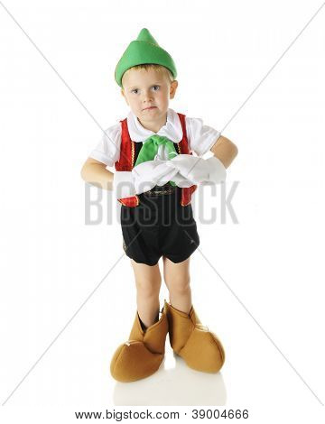 Full-length image of an adorable preschooler dressed as the puppet Pinocchio without his strings.  On a white background.