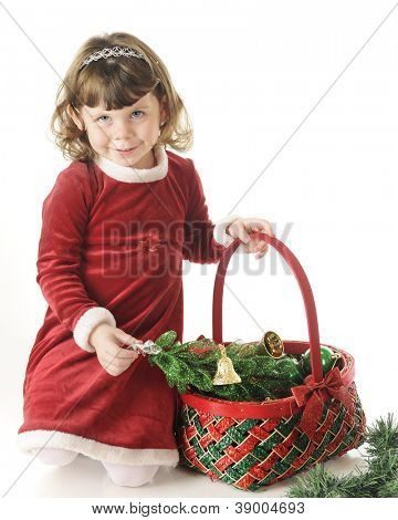A beautiful preschooler shyly smiling at the viewer kneeling in  her red dress holding a Christmas basket.  On a white background.