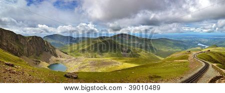 Panorama of the mountains of Snowdonia looking from Mount Snowdon, with a vintage steam train climbing from the town of LLanberis to the summit.