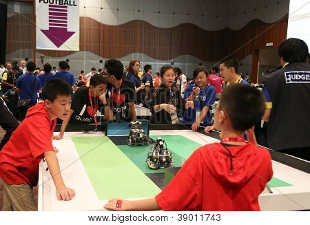 SUBANG JAYA - NOVEMBER 10: Unidentified team members cheer their robots playing in a football match at the World Robot Olympaid on November 10, 2012 in Subang Jaya, Malaysia.