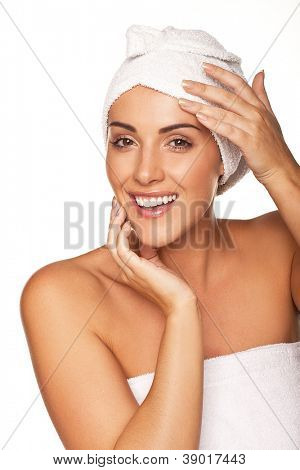 Vivacious beautiful woman wrapped in a white towel smiling and laughing as she feels rejuvenated after a spa treatment isolated on white