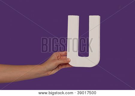 Female hand holding up the uppercase capital letter U isolated against a purple background conceptual of the alphabet, writing, literature and typeface