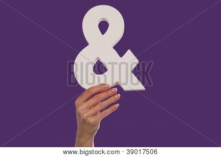 Female hand holding up a white ampersand symbol isolated against a purple background signifying plus, and, in conjunction with, or jointly