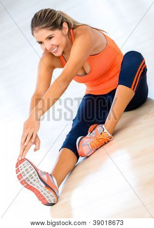 Atheltic woman stretching her leg at the gym