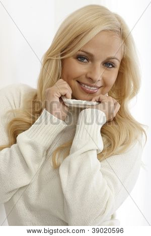 Portrait of beautiful young blonde woman in white turtleneck pullover.