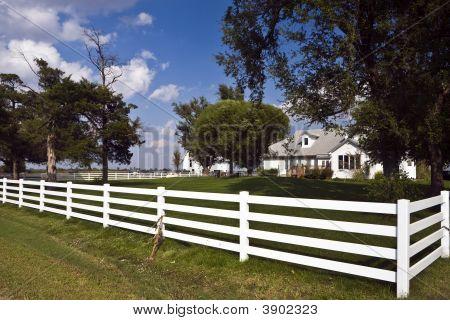 Fenced Farmhouse And Barn