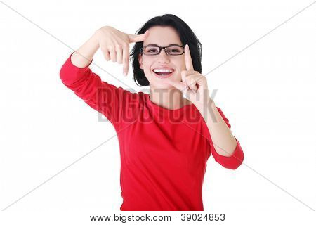 Smiling woman wearing red blouse is showing frame by hands. Happy girl with face in frame of palms. Isolated on white background.