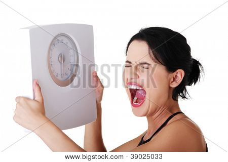Frustrated woman with scale, isolated on white