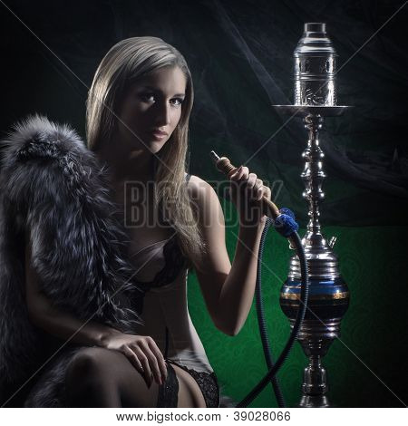 Young sexy woman in luxury underwear smoking the hookah