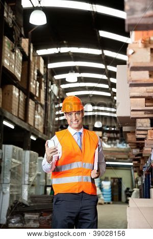 Portrait of young male supervisor in orange protective vest using cell phone at warehouse