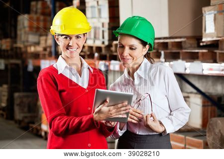 Portrait of female supervisor with colleague working together in warehouse