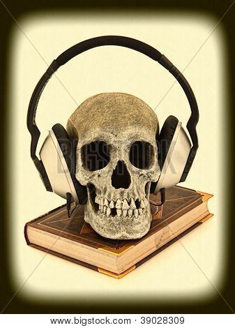 Scary, Haunted, Horror Audiobook concept with human skeleton wearing audio headset sitting on book.