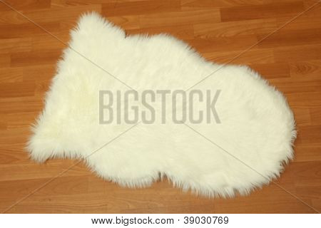 Decorative fur carpet on wooden floor