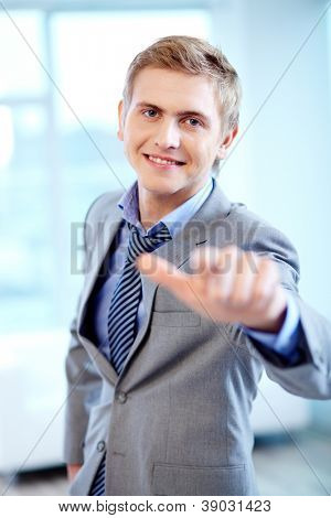 Portrait of cheerful businessman looking at camera while pointing at you