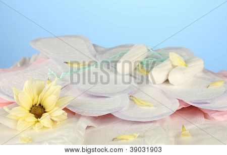 various types of sanitary pads and tampons on blue background close-up