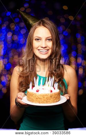 Portrait of joyful girl holding birthday cake with candles and looking at camera at party